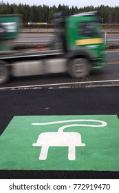 Stock photo of electric vehicle charging sign applied on asphalt at roadside, one vehicle driving by.