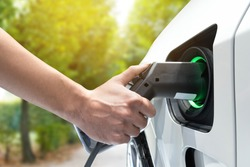 Electric vehicle charging station. Hand charging an electric car (EV) with the power cable supply plugged in.Flare light effect