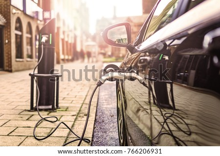 Electric Vehicle is changing in street.