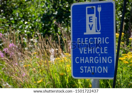 Electric vehicle only charging station sign for environmentally friendly vehicles with a green grass and flower background. #1501722437