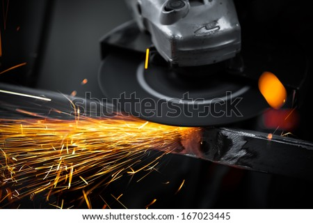Electric wheel grinding on steel structure in factory