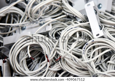 Electric white cable. Wire wound into skeins and rings. Electric wire cable product.  Connect the source of electric current with the consumer, components of the electrical circuit. Industrial details #409067512