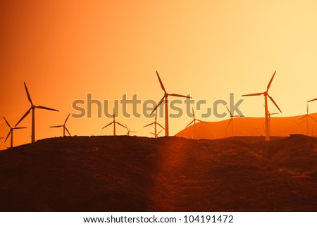 Electric wind turbines farm silhouettes on sun background