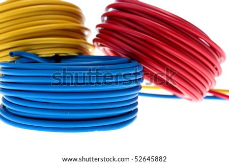 Electric wires of red, yellow and dark blue colour are winded in rings. - stock photo