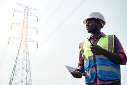 Electrical Africa American engineer with high voltage electricity pylon and using walkie talkie and tablet to control assistant. Electrical power lines and towers at sunset.