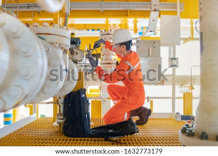 Electrical and instrument technician fix the valve at offshore oil and gas processing platform, maintenance and service occupational at oil rig.