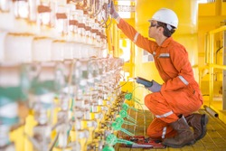 Electrical and instrument technician maintenance electric system at offshore oil and gas processing platform he using hand held calibrator an digital multi meter to calibrate choke valve.