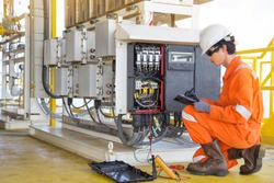 Electrical and instrument technician measuring voltage of thermo electric generator and record reading value to maintenance sheet for annual inspection at offshore oil and gas remote platform.