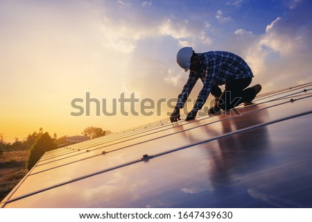 Electrical and instrument technician use wrench to fix and maintenance electric system at solar panel field with sunset sky reflection