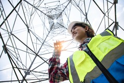 Electrical Asian beautiful engineer control projects under high voltage electricity pylon and using walkie talkie and tablet to control assistant. Electrical power lines and towers at blue sky.