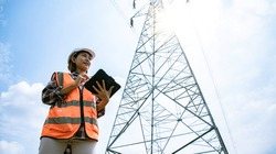 Electrical Asian beautiful engineer with high voltage electricity pylon and using walkie talkie and tablet to control assistant. Electrical power lines and towers at blue sky.