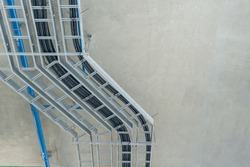 Electrical cable tray for cable routing between electrical distribution panel with equipment at bottom of upper floor. Selective focus.