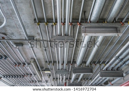 Electrical conduit for cable routing between electrical distribution panel with equipment at bottom of upper floor. Selective focus. Stock photo ©