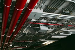 Electrical conduits system and metal pipeline installed on building ceiling.