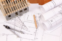 Electrical diagrams, accessories for engineer jobs and house under construction lyin on desk, concept of building home