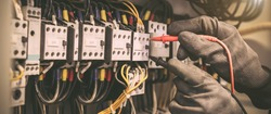 Electrical engineer using digital multi-meter measuring equipment to checking electric current voltage at circuit breaker in main power distribution board.