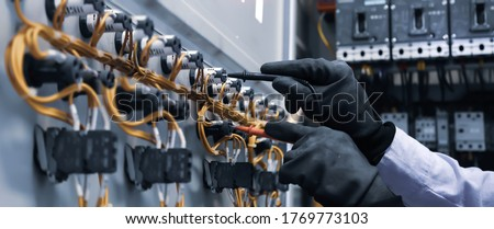 Electrical engineer using digital multi-meter measuring equipment to checking electric current voltage at circuit breaker in main power distribution board. Stockfoto ©