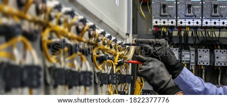 Electrical engineer using measuring equipment to checking electric current voltage at circuit breaker and cable wiring system for maintenance in main power distribution board. Сток-фото ©