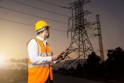 Electrical engineer working. Electrician holding mobile phone (or tablet) and watching on high voltage power of electricity pylon in sunrise