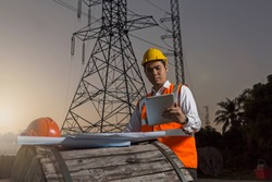 Electrical engineer working. Electrician holding tablet and working at high voltage power pylon construction site while sunrise.