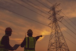 Electrical engineers and repair workers watching electrical poles and substations with sunset backgrounds
