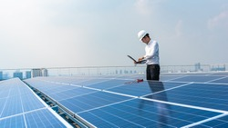 Electrical engineers are using laptops to monitor the operation of the solar rooftop. Renewable energy concepts.