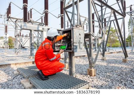 Electrical engineers inspect the electrical systems at the equipment control cabinet using data from the tablet