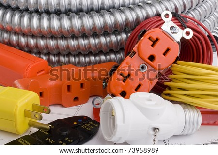 Electrical equipment laying on a series of electrical plans.