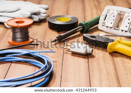 Electrical equipment, tools, cables and accessories used by an electrician on a wooden surface.