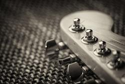 Electrical guitar head stock closeup. Sepia, vignette