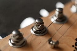 Electrical guitar headstock, machine heads and metal strings closeup. Electric guitar black and white color, detail. Music instruments. Concept international music day. Macrophotography. Soft focus