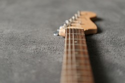 Electrical guitar neck, headstock and metal strings closeup. Electric guitar black and white color, detail. Music instruments. Concept international music day. Macrophotography. Soft focus