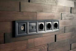 Electrical household switches and sockets close up. Minimalist interior design. Stylish bedroom and livingroom. Wooden bricks wall in a designer minimalist living room. Wooden parquet room