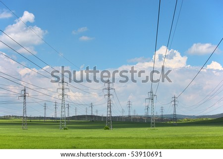 Electrical net of poles on a panorama of blue sky and green meadow