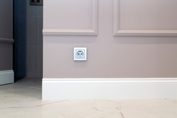 electrical outlet on the brown wall above the baseboard and marble floor