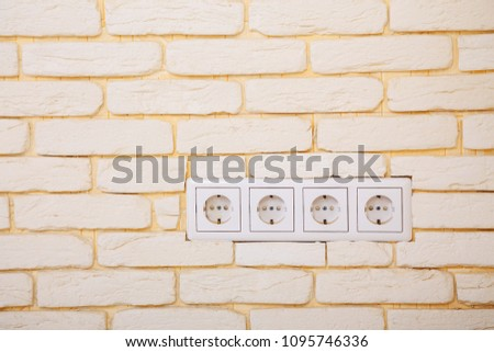 electrical outlets, four network sockets in the white brick wall, home electricity