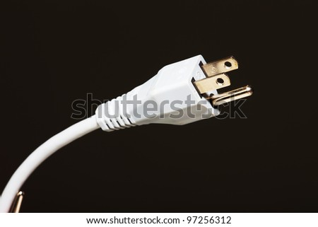 Electrical plug over black background.