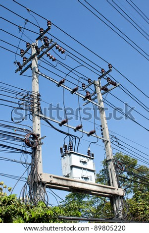 electrical post by the road with power line cables, transformers and phone lines