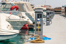 Electrical power sockets bollard on pier near sea coast. Charging station for boats in Mediterranean. Electrical outlets to charge ships in harbor.