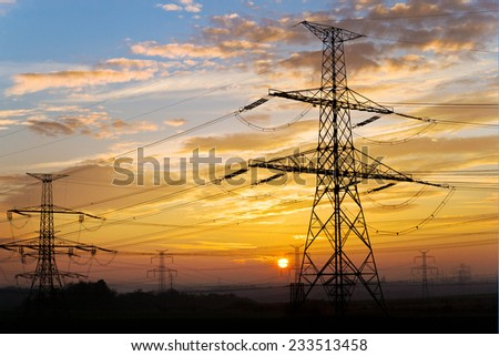Electrical pylon and high voltage power lines near transformation station at sunset, Czech republic