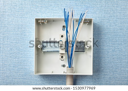 Electrical services to fuse board upgrades. Electricity supply and consumer unit in a house. Metal mounting straight edge guide DIN rail. Home circuit breaker setup. Electric installation work.