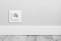 Electrical socket isolated on gray wall. Renovated studio apartment power supply background. Empty copy space single white plastic power outlet.