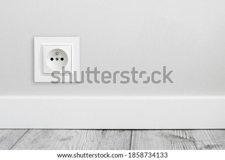 Electrical socket isolated on gray wall. Renovated studio apartment power supply background. Empty copy space single white plastic power outlet. Photo stock ©