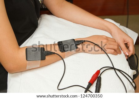 Electrical stimulation forearm ,physical therapist helping woman with ...