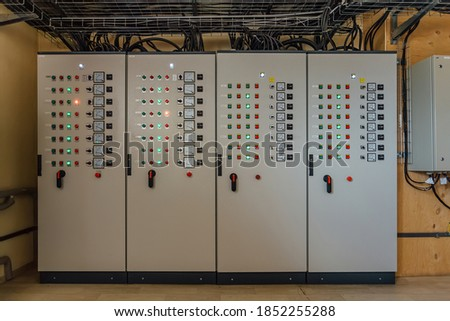 Electrical switchgear cabinets with control panels with indicator lights in factory. Stockfoto ©