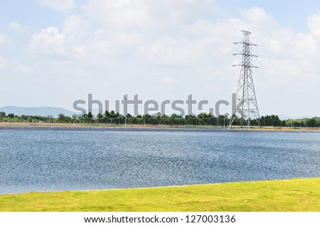 Electrical tower across the lake on a background of the blue sky