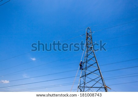 Electrical Tower Cable Maintenance  Electricians climb steel metal pylon tower for cable maintenance against blue sky