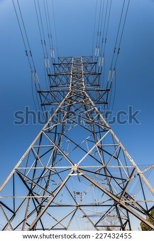 Electrical  Tower Cables Electrical high voltage power-lines tower metal structure attached cables in blue sky