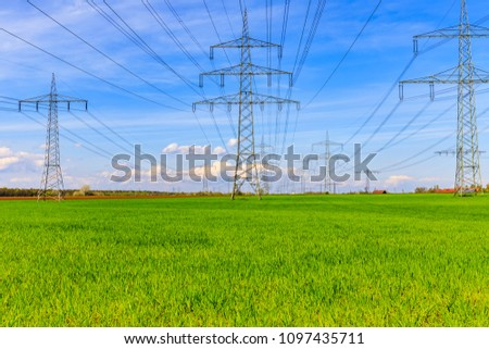 Electrical towers. Power transmission Electrical line on blue sky, green  field background, ancient rural landscape and modern powerlines technology, Germany, #1097435711