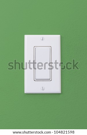 Electrical white rocker light switch on green wall
